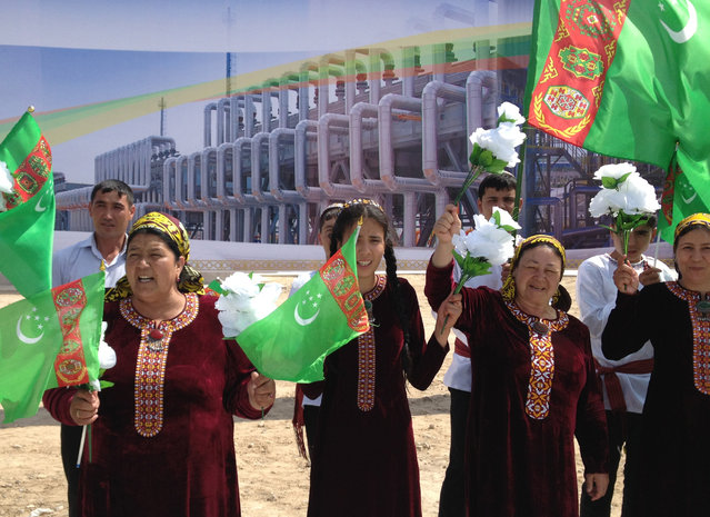 People wearing traditional dresses wave national flags in front of a poster as they attend an opening ceremony of a new gas processing plant at Bagtyarlyk gas field in eastern Turkmenistan May 7, 2014. (Photo by Marat Gurt/Reuters)