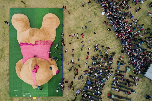 In this aereal view officials measure a teddy bear measuring more than 20 meters long and 4 tons of weight, which entered the Guiness Book of World Records as the biggest of its kind on April 28, 2019 in Xonacatlan, Mexico state. (Photo by Mario Vazquez/AFP Photo)