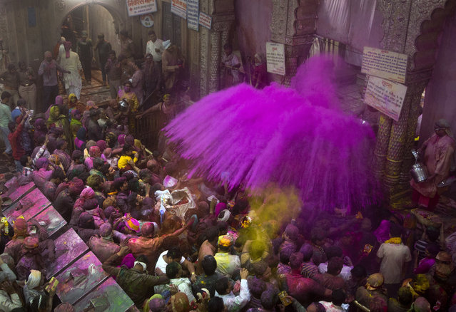 Hindu priests throw color powders at the devotees inside Banke Bihari temple, dedicated to Lord Krishna, during Holi festival celebrations in Vrindavan, India, Wednesday, March 8, 2017. Holi, the festival of colors, celebrates the arrival of spring. (Photo by Manish Swarup/AP Photo)