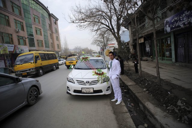 A groom stands next to his car as he poses for a photograph just after leaving a barber shop in Kabul March 6, 2014. (Photo by Morteza Nikoubazl/Reuters)