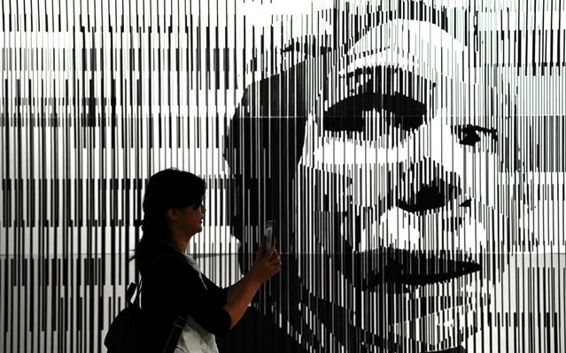 """A visitor takes a photo of an art work entitled """"Anxiety"""" during a """"Tape Art"""" exhibition by Tape That, an artist collective based in Berlin, in Taipei on July 16, 2019. The exhibition is on display until September 1. (Photo by Sam Yeh/AFP Photo)"""