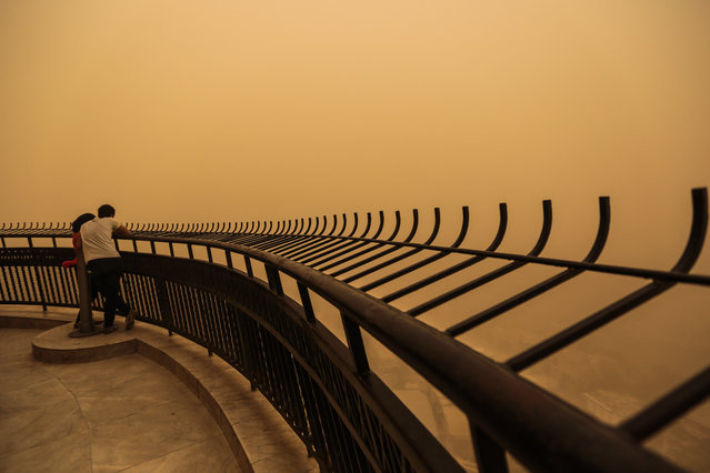 A couple observe a sandstorm that shrouds the capital city from an observation deck of the Cairo Tower in Zamalek, Cairo, Egypt, Saturday, June 27, 2015. (Photo by Mosa'ab Elshamy/AP Photo)