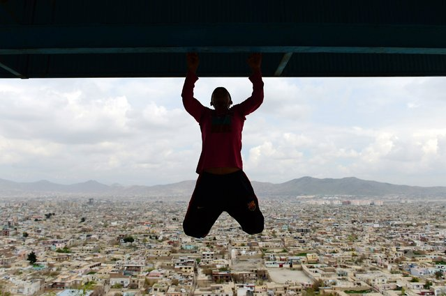 An Afghan youth exercises at Wazir Akbar Khan hilltop overlooking Kabul on April 18, 2014. Football is a popular sport in the war-torn country, with the Afghan national football team winning last year's South Asian Football Championship. (Photo by Wakil Kohsar/AFP Photo)