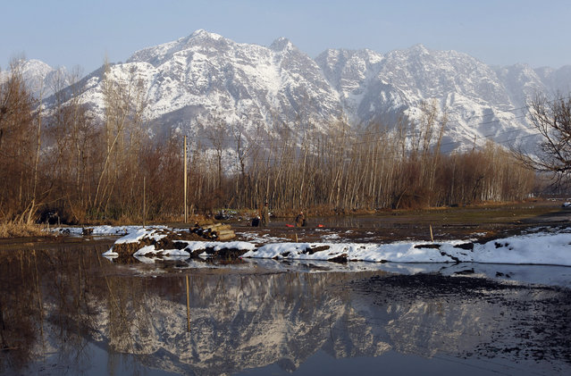 Framed by the Zabarwan Hills, a Kashmiri man sits by Dal Lake on a sunny day, in Srinagar January 2, 2011. (Photo by Danish Ismail/Reuters)