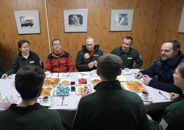 """Russian President Vladimir Putin, center, and Prime Minister Dmitry Medvedev, second left, listen to the employees of the """"Omega"""" field base in the Russian Arctic National Park on the Franz Josef Land archipelago, Russia, Wednesday, March 29, 2017. (Photo by Alexei Druzhinin, Sputnik, Kremlin Pool Photo via AP Photo)"""