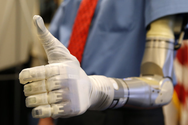 Vietnam veteran Fred Downs gives a thumbs up during a demonstration of modular prosthetic arm technology developed by the Defense Advanced Research Projects Agency (DARPA) at the Pentagon in Washington April 22, 2014. (Photo by Kevin Lamarque/AFP Photo)