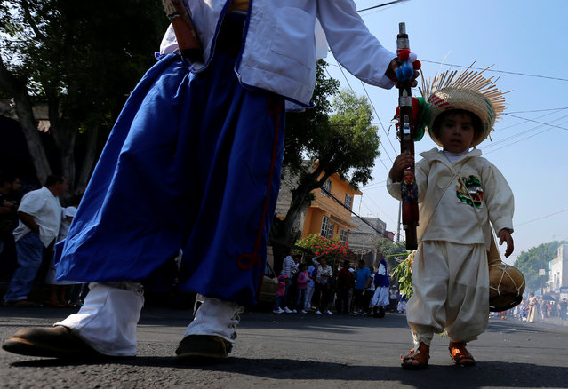 A boy and his father wearing a period costume re-enacts the battle of Puebla, take part along the streets in the Penon de los Banos neighbourhood of Mexico City, Mexico May 5, 2016. (Photo by Henry Romero/Reuters)