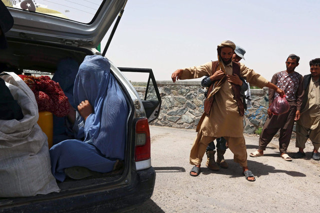 An Afghan policeman frisks a man while a burqa-cald woman sits in the trunk of a car on a roadside in Herat, Afghanistan, 05 July 2015. At least 18 police, two civilians and 30 rebels were killed in central Afghanistan during three days of fierce fighting, police said on 04 July. The clashes ended 04 July after security forces retook control of nine police checkpoints that had fallen to the rebels. (Photo by Jalil Rezayee/EPA)