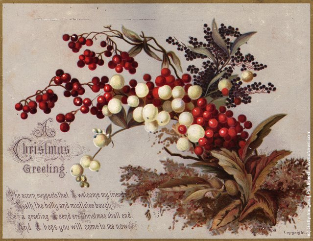 1882: Traditional holly berries and sprigs of mistletoe decorate a Victorian Christmas greetings card