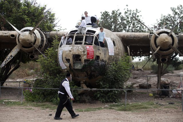 """Israeli boys play on an old Israeli military transport plane """"Nord"""" in the so-called Defender's Forest, near Kibbutz Nachson, as they visit the area for a picnic on Israel's 66th Independence Day, 06 May 2014. The plane had been placed here as part of a memorial to fallen soldiers in the 1967 Middle East War. The plane was used by the Israeli Air Force during the 1967 Six Day War as a troop transporter. Israel's flock en mass to parks and beaches to cook outdoors and enjoy family picnics during Independence Day. Many also visit military bases to view army equipment. (Photo by Abir Sultan/EPA)"""