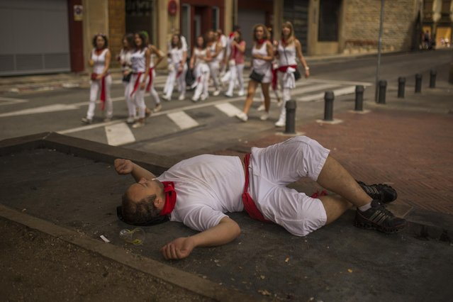 A man sleeps on the street as revelers walk by after the running of the bulls at the San Fermin festival in Pamplona, Spain, Saturday, July 11, 2015. (Photo by ndres Kudacki/AP Photo)
