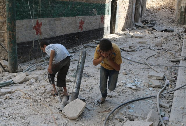 Boys cover their ears as they play with a pipe, pretending it is a mortar, at a site hit by what activists said was a barrel bomb dropped by forces loyal to Syria's President Bashar al-Assad in the old city of Aleppo, Syria July 12, 2015. (Photo by Abdalrhman Ismail/Reuters)