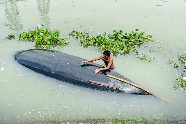 A man cleans his boat in Buriganga River in Dhaka, Bangladesh on September 22, 2019. (Photo by Munir Uz Zaman/AFP Photo)
