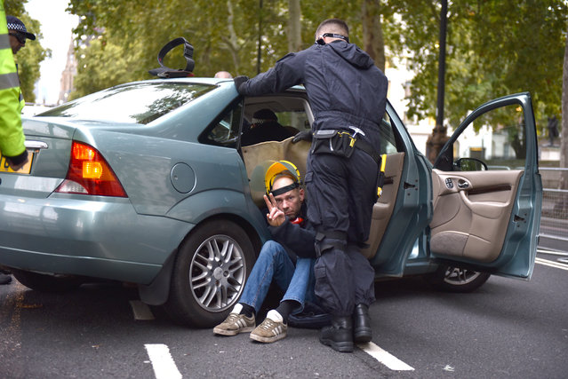 Protesters chained across the seats of a car are removed by the police on the Embankment in Westminster as Extinction Rebellion launch their two week long protest on October 07, 2019 in London, England. (Photo by John Keeble/Getty Images)