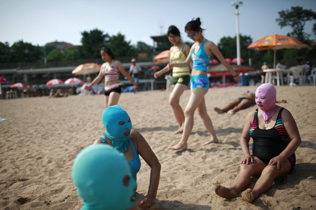 Women, wearing nylon masks, rest on the shore as youths walk past them during their visit to a beach in Qingdao, Shandong province, China, July 6, 2012. (Photo by Aly Song/Reuters)