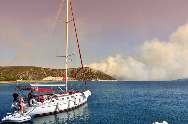 Tourists embark at a sailing boat as a wild fire burns on the mountain near the town of Nafplio, about 140km southwest (87 miles) of Athens, Friday, July 17, 2015. At least four other wildfires broke out across the country, including one north of the Greek capital. Greece applied for assistance from other European countries. (Photo by Vangelis Bougiotis/InTime News via AP Photo)