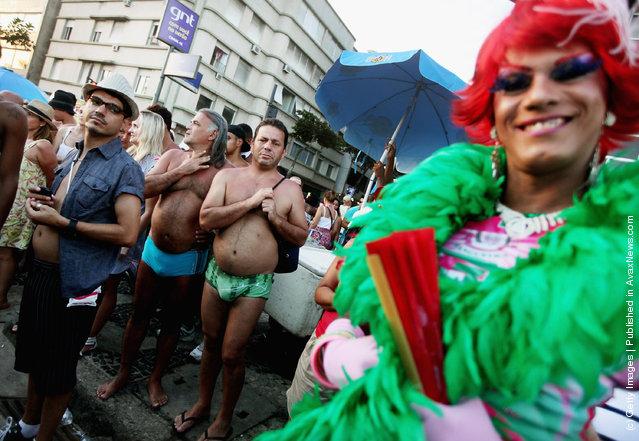 Brazilian revelers watch Carnival celebrations along Ipanema beach in Rio de Janiero