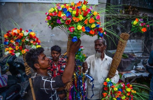 Vendors sell artificial flowers at a roadside market on the eve of the Chhath Puja Festival in Siliguri on November 1, 2019. The Chhath Festival, also known as Surya Pooja, or worship of the sun, is observed in some parts of the northern Indian states, and sees devotees worshipping the sun god on the banks of rivers or small ponds, and praying for the longevity and health of their spouse. (Photo by Diptendu Dutta/AFP Photo)