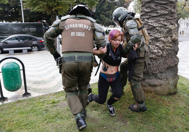 A demonstrator is detained by riot police during an unauthorized march called by secondary students to protest against government education reforms in Valparaiso, Chile, May 26, 2016. (Photo by Rodrigo Garrido/Reuters)