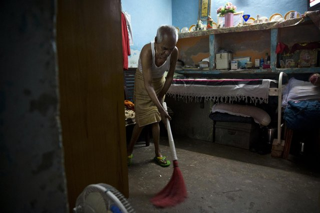 """In this June 8, 2015 photo, Omkarnath, who goes by the name """"Medicine Baba"""", sweeps the floor of his rented accommodation at a fetid slum in New Delhi, India. (Photo by Saurabh Das/AP Photo)"""