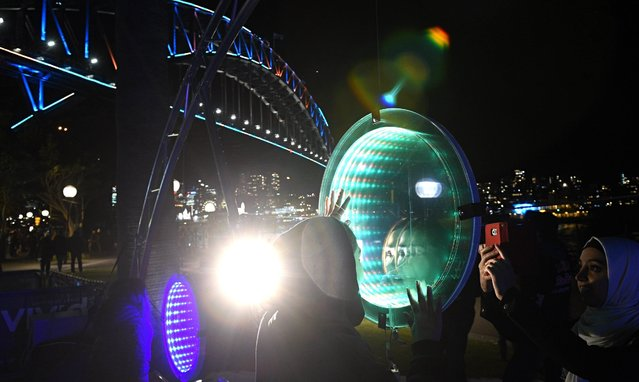 People take picture in front of an installation as the Sydney Harbour Bridge (L, back) is lit in blue during the official opening night of the Vivid Sydney 2016 in Sydney, Australia, 27 May 2016. The annual outdoor lighting festival runs from 27 May until 18 June 2016. (Photo by Sam Mooy/EPA)