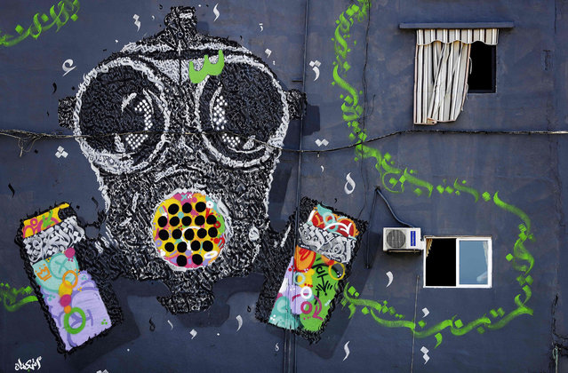 A mural painting by the Lebanese steet artists group Ashekman covers the wall of a building in the highly polluted area of Karantina on the outskirts of the capital Beirut on October 7, 2019. Greenpeace MENA collaborated with Ashekman, to create a mural the mural painting in order to grab attention on the issue of air pollution. (Photo by Joseph Eid/AFP Photo)