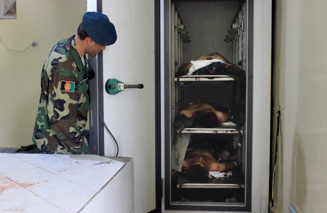 An Afghan soldier looks at lifeless bodies of men who were killed by Taliban militants in Kunduz province northern of Kabul, Afghanistan, Tuesday, May 31, 2016. An Afghan official says the Taliban have attacked several buses on a road in the country's north, killing many people and abducting at least 35. (Photo by Najim Rahim/AP Photo)