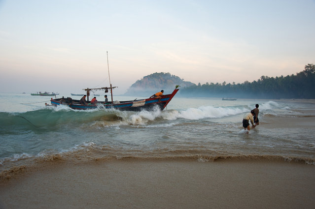 """""""Dawn landing"""". After a night out at sea fishing for squid the fishermen return to Ngapali beach at dawn with their catch. Photo location: Ngapali Beach, Myanmar. (Photo and caption by Malcolm McDougall/National Geographic Photo Contest)"""