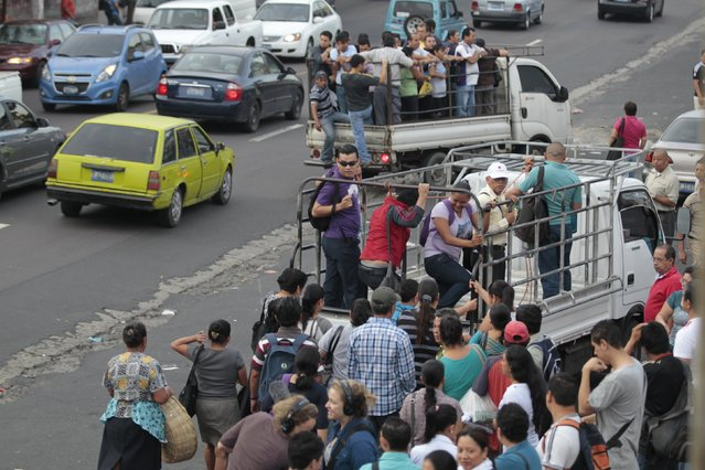 People try to board a pick up truck during the second day of a suspension of public transport services in Mejicanos, El Salvador July 28, 2015. (Photo by Jose Cabezas/Reuters)