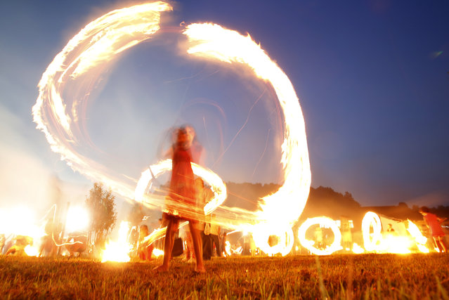 Bosnian children wave burning bark during celebrations of  St. Ilija at the village Dokanj norheastern Bosnia, near Tuzla, late night Sunday, July 19, 2015. (Photo by Amel Emric/AP Photo)