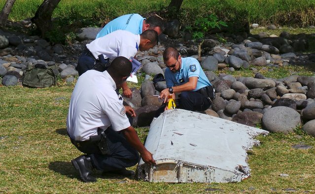 French gendarmes and police inspect a large piece of plane debris which was found on the beach in Saint-Andre, on the French Indian Ocean island of La Reunion, July 29, 2015. France's BEA air crash investigation agency said it was examining the debris,  in coordination with Malaysian and Australian authorities, to determine whether it came from Malaysia Airlines Flight MH370, which vanished last year in one of the biggest mysteries in aviation history. (Photo by Prisca Bigot/Reuters/Zinfos974)