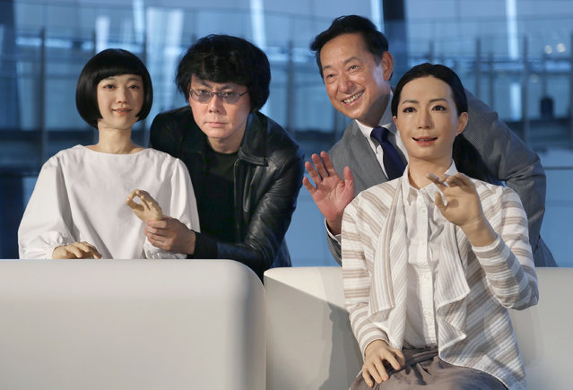 Japanese android expert Hiroshi Ishiguro, second left, and National Museum of Emerging Science and Innovation Miraikan Chief Executive Director Mamoru Mohri, second right, pose with a female-announcer robot called Otonaroid, right, and a girl robot called Kodomoroid during a press unveiling of the museum's new guides in Tokyo Tuesday, June 24, 2014. (Photo by Shizuo Kambayashi/AP Photo)