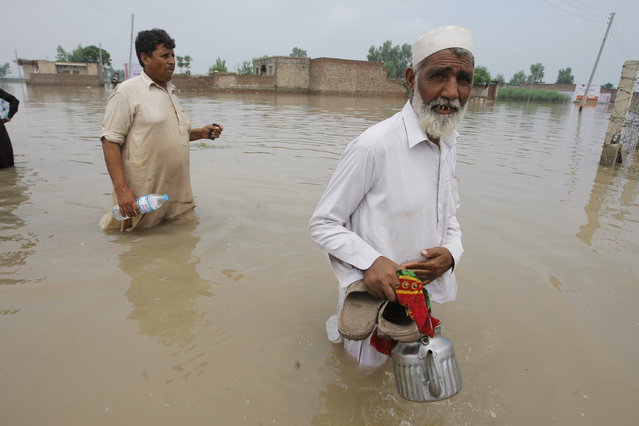 Pakistani flood victims wade through floodwater to reach their homes in Peshawar, Pakistan, Monday, August 3, 2015. (Photo by Mohammad Sajjad/AP Photo)