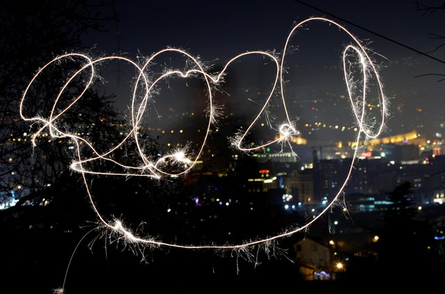 A girl with sparkle writes 2020 during New Year celebration , North Macedonia on January 1, 2020. (Photo by Ognen Teofilovski/Reuters)