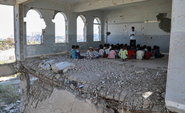 Yemeni children attend class on the first day of the new academic year in the country's third-city of Taez on September 3, 2019, at a school that was damaged last year in an air strike during fighting between the Saudi-backed government forces and the Huthi rebels. (Photo by Ahmad Al-Basha/AFP Photo)