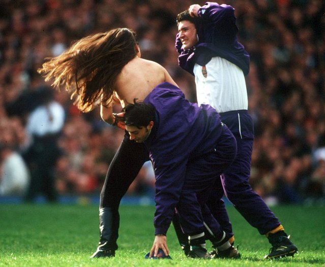 A female streaker is apprehended by ground staff after she ran topless on to the field during the England v Wales 5 nations rugby match at Twickenham, England, on March 19, 1994. (Photo by David Cannon/Allsport)