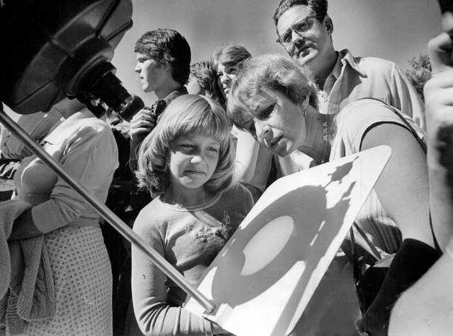 Mrs. Reggie Billings and her 7-year- old daughter, Rene, were in a crowd at Gates Planetarium in City Park to view partial eclipse of sun in 1977. Twenty- four per cent of the sun disappeared about 2:35 p.m. Wednesday as the  shadow of the moon crossed its surface. Gates set up a telescope for public viewing. The sun, left, took on the aspect of a moon when the moon passed between it and earth. Photograph taken at the National Oceanic and Space Environment  Laboratory in Boulder shows intervening moon and a temporary facet of the sun-a flare. The flare, which normally disturbs radio communications on earth, appears as light spots at center. (Photo by Duane Howell/The Denver Post)