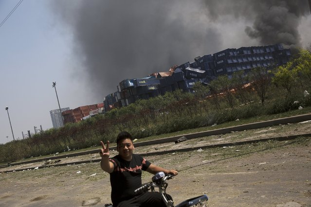 A man shows the victory sign at the explosion site in Binhai new district in Tianjin, China August 13, 2015. (Photo by Damir Sagolj/Reuters)
