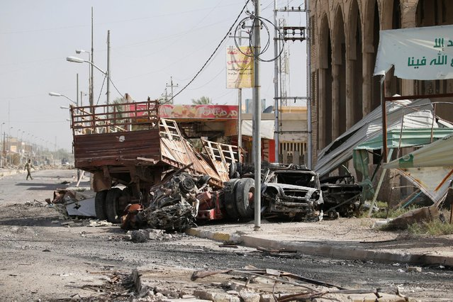 Destroyed vehicles are seen in Falluja, Iraq, June 26, 2016. (Photo by Thaier Al-Sudani/Reuters)