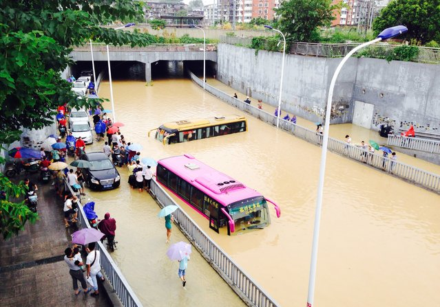 Vehicles are submerged in a flooded street, July 24, 2014, in Fuzhou, China. Typhoon Matmo landed July 23 with gales and heavy rainfalls in and around China. (Photo by ChinaFotoPress/Getty Images)