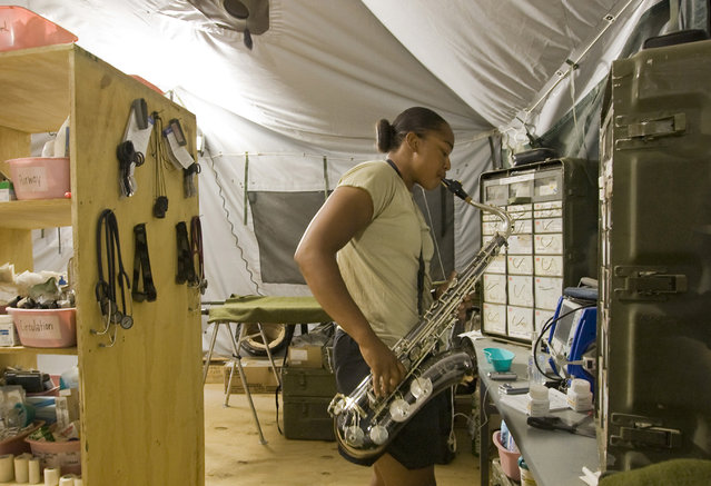 U.S. Combat Medic Health Care Specialist Seantella Cottner of the 3rd Brigade, 10th Mountain Division plays the saxophone in her Forward Aid Station tent on the Combat Operation Outpost (COP) McClain in Logar Province in Afghanistan July 22, 2009. (Photo by Shamil Zhumatov/Reuters)