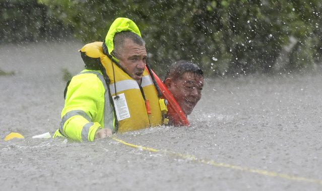Wilford Martinez, right, is rescued from his flooded car by Harris County Sheriff's Department Richard Wagner along Interstate 610 in floodwaters from Tropical Storm Harvey on Sunday, August 27, 2017, in Houston, Texas. (Photo by David J. Phillip/AP Photo)