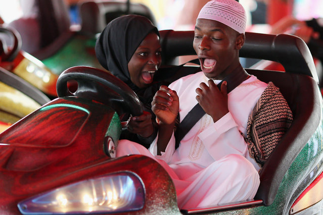 People ride on Bumper cars during an Eid celebration in Burgess Park on July 28, 2014 in London, England. The Muslim holiday Eid marks the end of 30 days of dawn-to-sunset fasting during the holy month of Ramadan. (Photo by Dan Kitwood/Getty Images)