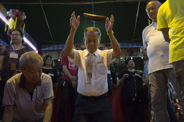 """In this September 3, 2017, photo, a man throws wooden moon blocks to request an answer from the gods, at a makeshift altar during the """"Hungry Ghost Festival"""" in Hong Kong. (Photo by Kin Cheung/AP Photo)"""