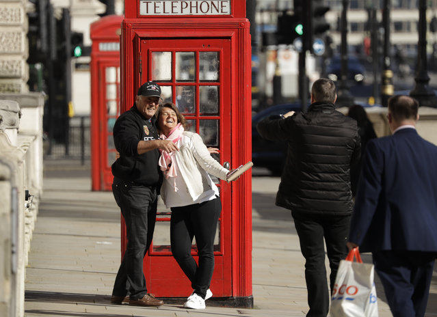 Two tourist have their photo taken next to a traditional red telephone box in Westminster, London, Monday, March 23, 2020. The British government is encouraging people to practice social distancing to help prohibit the spread of Coronavirus, further restrictions may be imposed if the public do not adhere to their advice. (Photo by Matt Dunham/AP Photo)