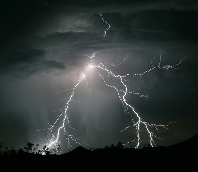 Lightning strikes near the town of Searchlight, Nevada as the first storm of the season passes through the western deserts of the United States in the early hours of June 8, 2006. (Photo by Gene Blevins/Reuters)
