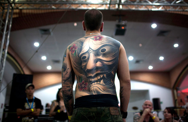 A man shows his tattoos as he attends the Venezuela Expo Tattoo in Caracas, Venezuela, on January 28, 2012. (Photo by Ariana Cubillos/AP Photo)