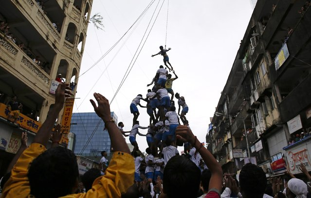 Devotees tumble as they try to form a human pyramid, on August 18, 2014. (Photo by Danish Siddiqui/Reuters)