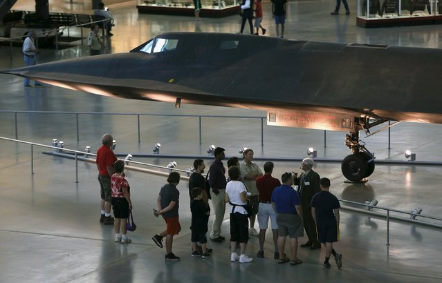 A tour group gathers under a Lockheed SR-71 Blackbird at the Udvar-Hazy Smithsonian National Air and Space Annex Museum in Chantilly, Virginia August 28, 2015. The SR-71 was a long-range spy plane that was in use from 1964 to 1998 and designed to operate at three times the speed of sound. (Photo by Gary Cameron/Reuters)