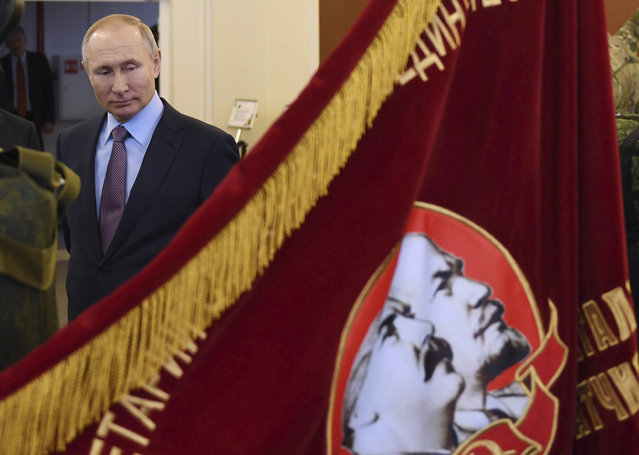 """Russian President Vladimir Putin looks at a Soviet era banner depicting Soviet Union founder Vladimir Lenin and Soviet dictator Joseph Stalin during his visit to the company """"Polyot"""", manufacturing parachute systems, in Ivanovo, 254 kilometers (158 miles) northeast of Moscow, Russia, Friday, March 6, 2020. Russian President Vladimir Putin said Friday he doesn't want to scrap presidential term limits or resort to other suggested ways of extending his rule, but otherwise he kept mum about his plans. (Photo by Alexei Nikolsky, Sputnik, Kremlin Pool Photo via AP Photo)"""